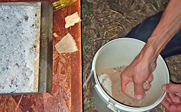 Räuchermehl wird aus einem Eimer entnommen und in die Räucherlade gefüllt.